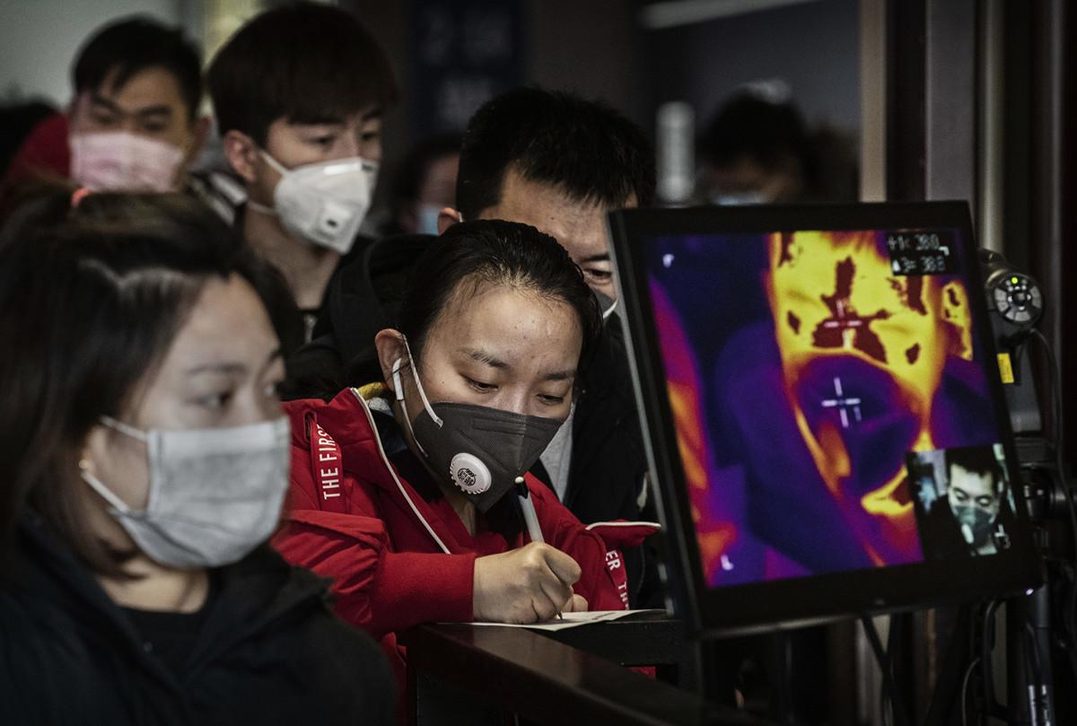 中共肺炎疫情持續延燒之際,年後迎來返程潮,首都機場和地鐵裏人頭攢動,給北京帶來疫情隱患。圖為31日,一名婦女在北京車站的體溫掃瞄儀前填寫表格。(Photo by Kevin Frayer/Getty Images)