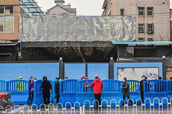 2月1日,世衛專家小組到達武漢封閉的華南海鮮批發市場時,中共警衛人員在外設置路障。(HECTOR RETAMAL/AFP via Getty Images)