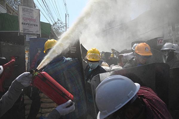 2021年3月8日,仰光民眾在街頭抗議軍事政變活動中,他們用滅火器驅散武警發射的煙霧彈。(STR/AFP via Getty Images)