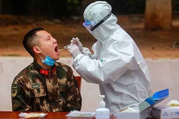 2020年2月11日,一名防疫人員在中國深圳,對一名武警進行COVID-19檢測。(STR/AFP via Getty Images)