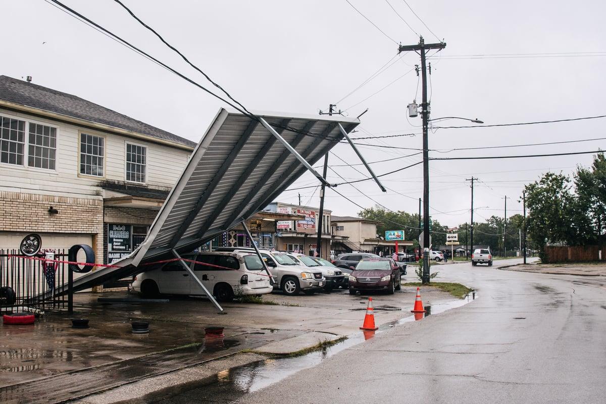 熱帶風暴尼古拉斯於 2021年9月14日在德州侯斯頓穿過該地區後,一個車庫頂懸掛在電線上。(Brandon Bell/Getty Images)