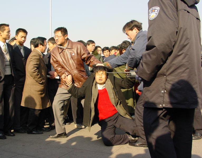 圖為一位法輪功學員在北京天安門廣場被便衣警察毆打。(明慧網)