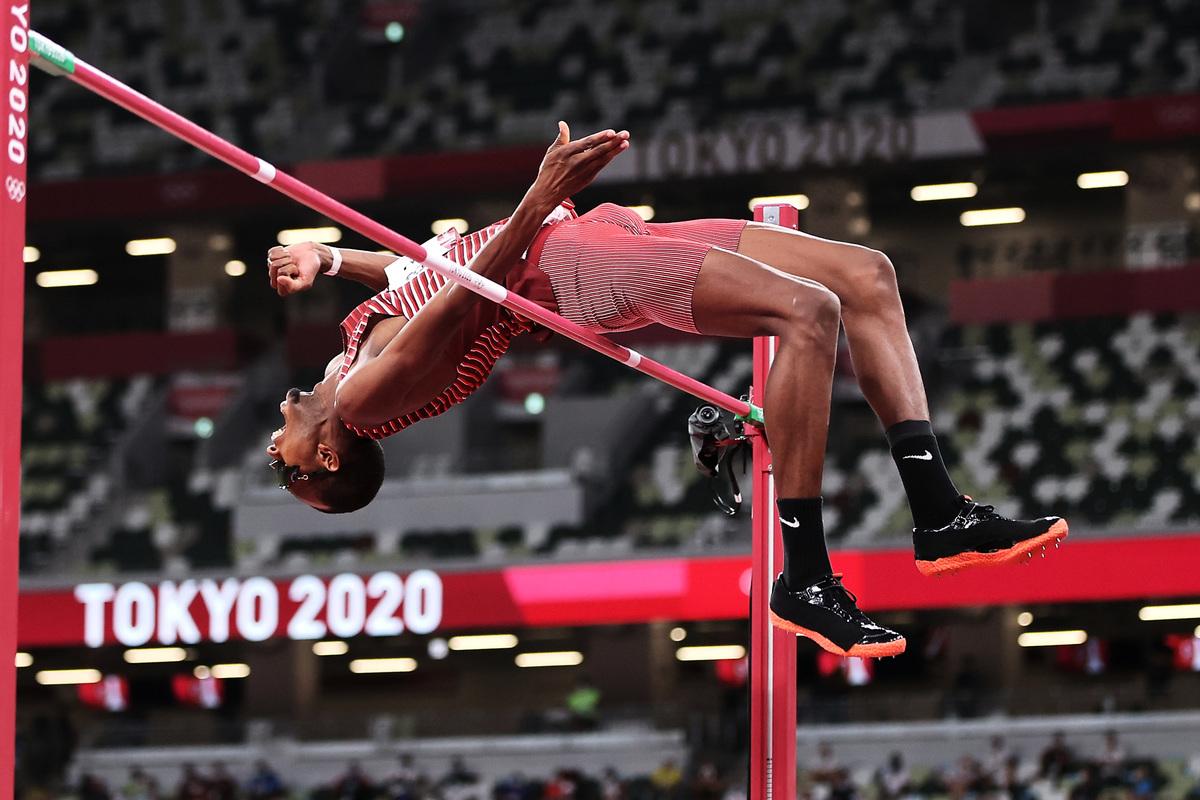 在東京奧運男子跳高決賽中,卡塔爾選手巴爾希姆越過橫桿瞬間。(Cameron Spencer/Getty Images)