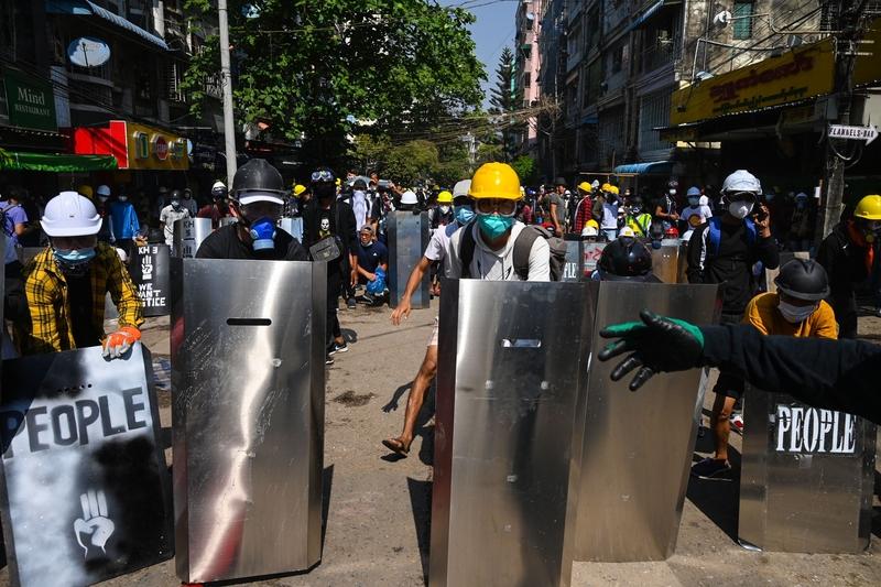 2021年3月8日,仰光民眾在街頭抗議軍事政變的大罷工中,帶著自製的簡易盾牌來防禦武警發射的催淚彈。(STR/AFP via Getty Images)