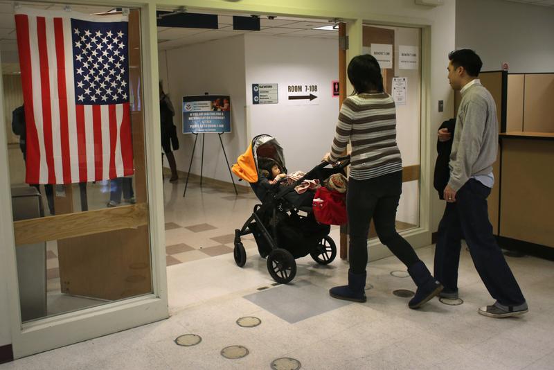 圖為2013年1月29日,一對中國夫婦帶著孩子走出紐約市的美國公民及移民服務局(USCIS)。 (John Moore/Getty Images)