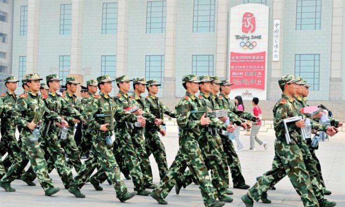 2008年4月29日,中共武警在北京天安門廣場邊上巡邏,經過北京奧運會倒計時鐘。在奧運會前,中共政權鎮壓了被視為持不同政見者的團體。(Teh Eng Koon/AFP/GETTY IMAGES)