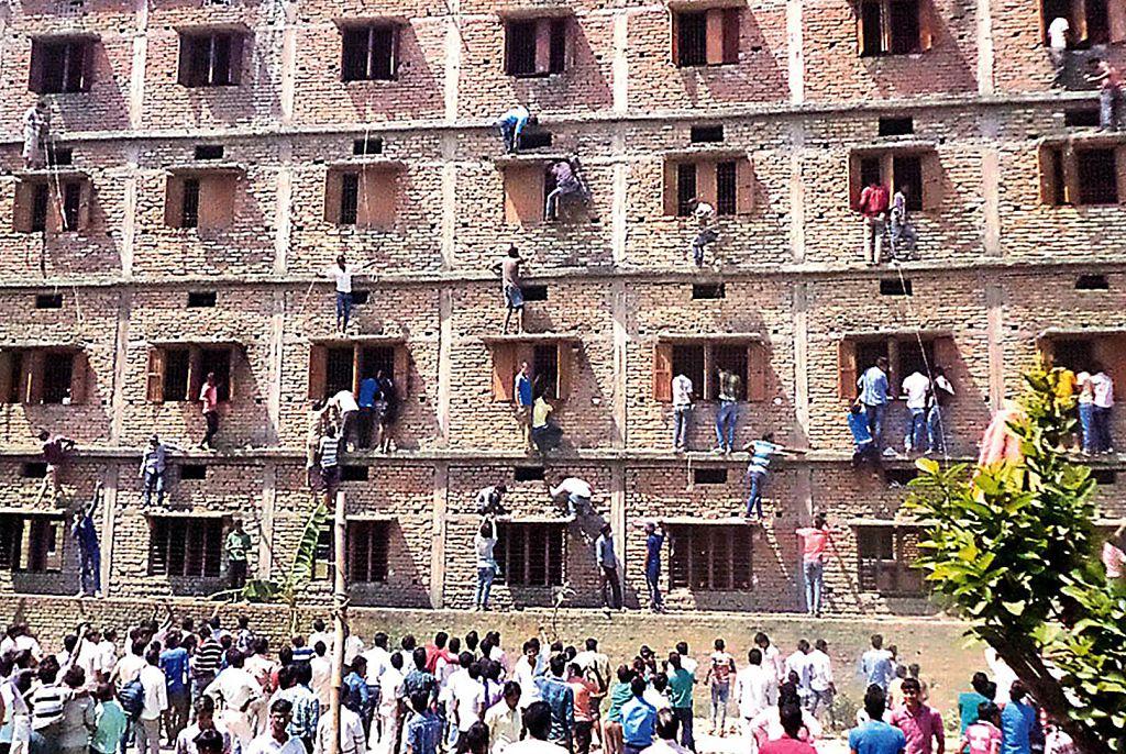這張照片攝於2015年3月19日,印度比哈爾州的學生親屬親屬爬上了考試大樓的牆壁,以幫助考生通過考試。(STRDEL/AFP/Getty Images)
