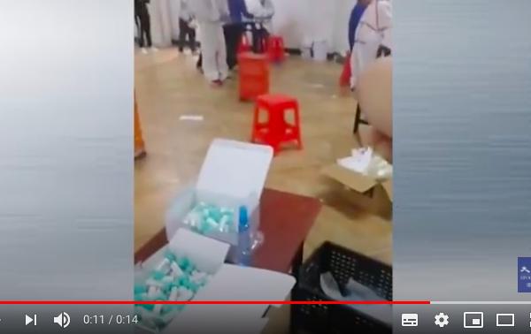 在做核酸檢測的工作檯邊,站著幾位檢測人員。旁邊的一位男士看到一位女性檢測人員沒有消毒,就告誡她們要消毒,否則就是在害人。(影片截圖)