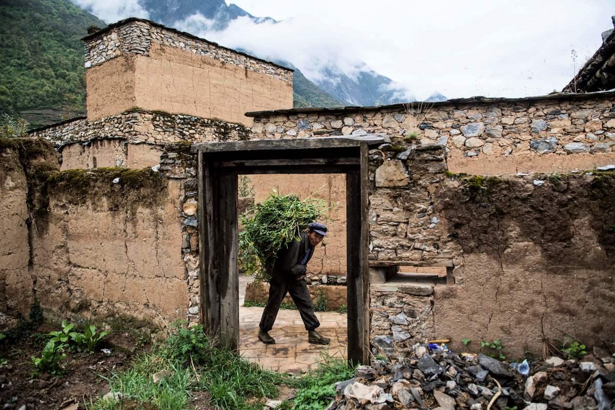 儘管中國2020年發生的地震、颱風、水災、疫情持續不斷,但是中共當局還是「按照既定方針」宣佈全國貧困縣全部「脫貧摘帽」。圖為2018年4月23日四川阿壩州村民正將牲畜的食物運送到老村落。(Johannes Eisele/AFP via Getty Images)