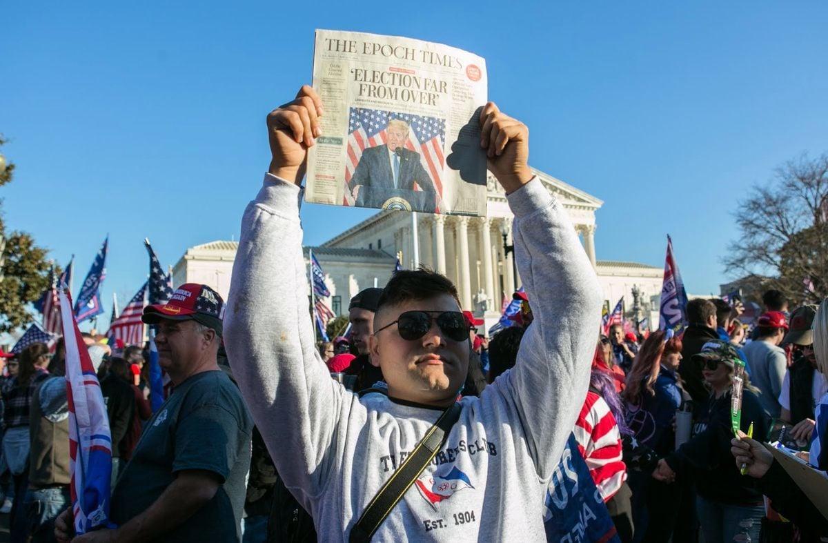 參加2020年11月14日華府遊行的民眾中有很多是大紀元的讀者。圖為一個讀者高高舉起大紀元報紙。(李莎/大紀元)