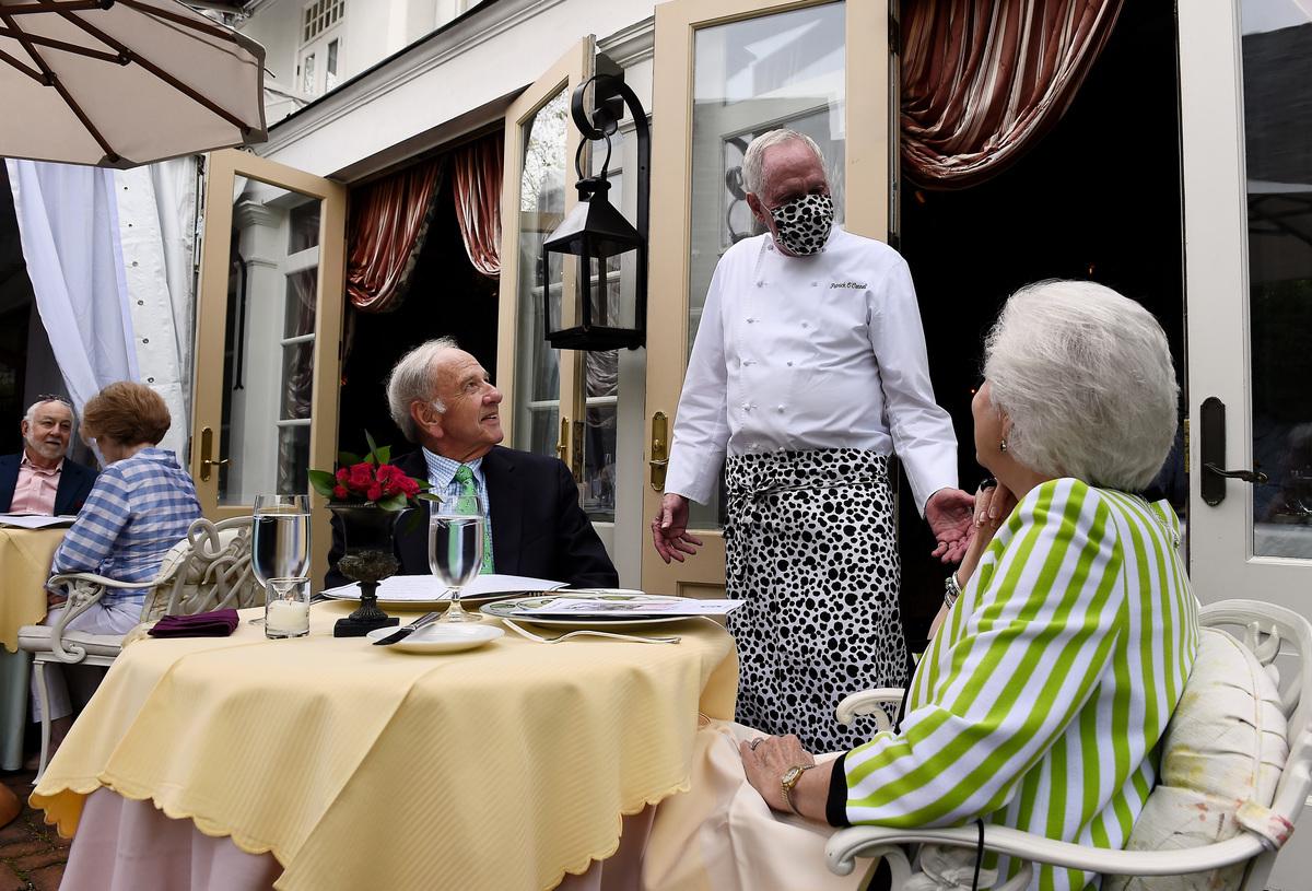 2020年5月29日,維珍尼亞州解封第一天,著名餐館Little Washington的主廚Patrick O'Connell戴著口罩與客人們交談。(OLIVIER DOULIERY/AFP via Getty Images)