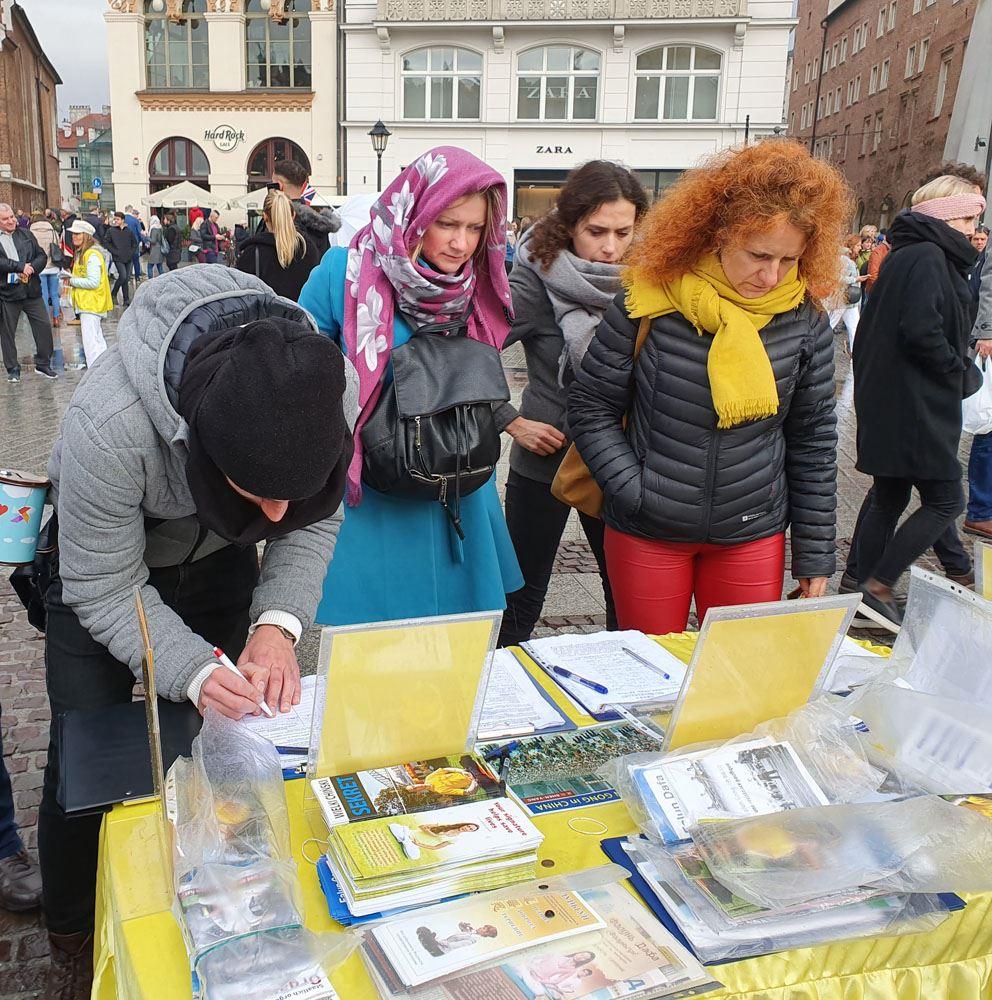 2019年11月9日至10日波蘭法輪功學員在克拉科夫市古城中央市集廣場向遊客展示功法,各國遊客簽名支持他們揭露中共迫害,舉報元兇江澤民。(明慧網)