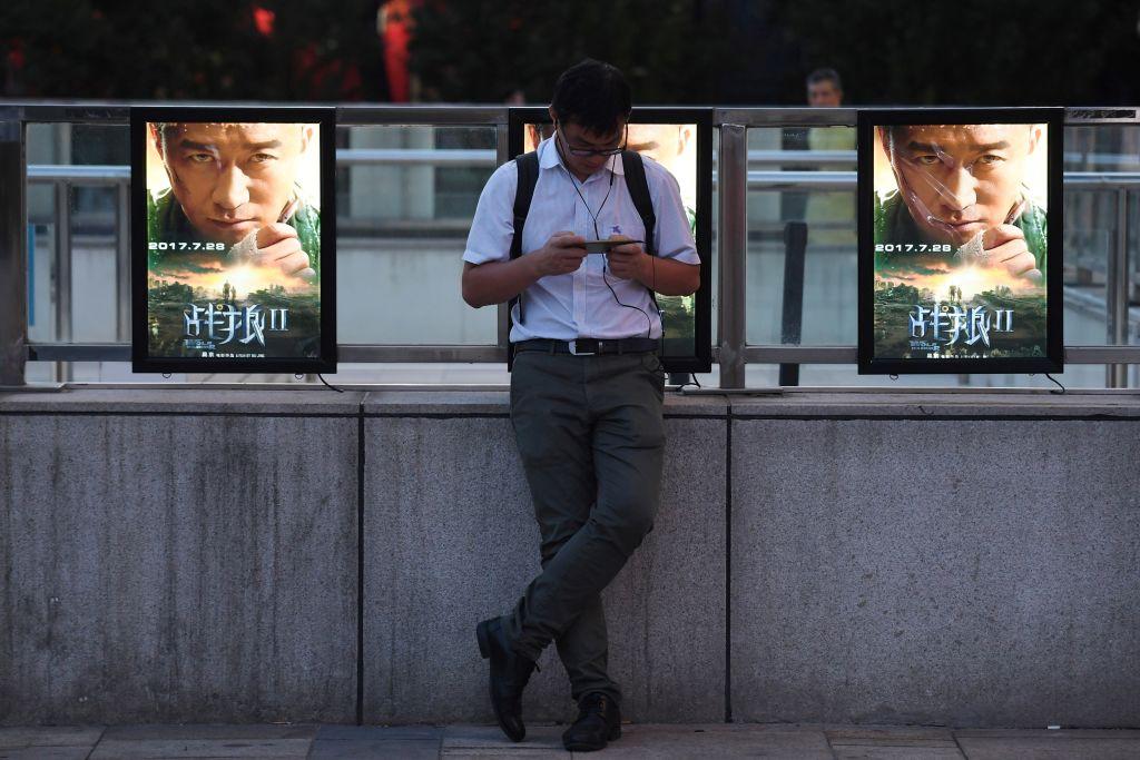 圖為北京街頭的一名男子站在由吳京導演及主演的電影《戰狼2》的海報前面。(GREG BAKER/AFP/Getty Images)