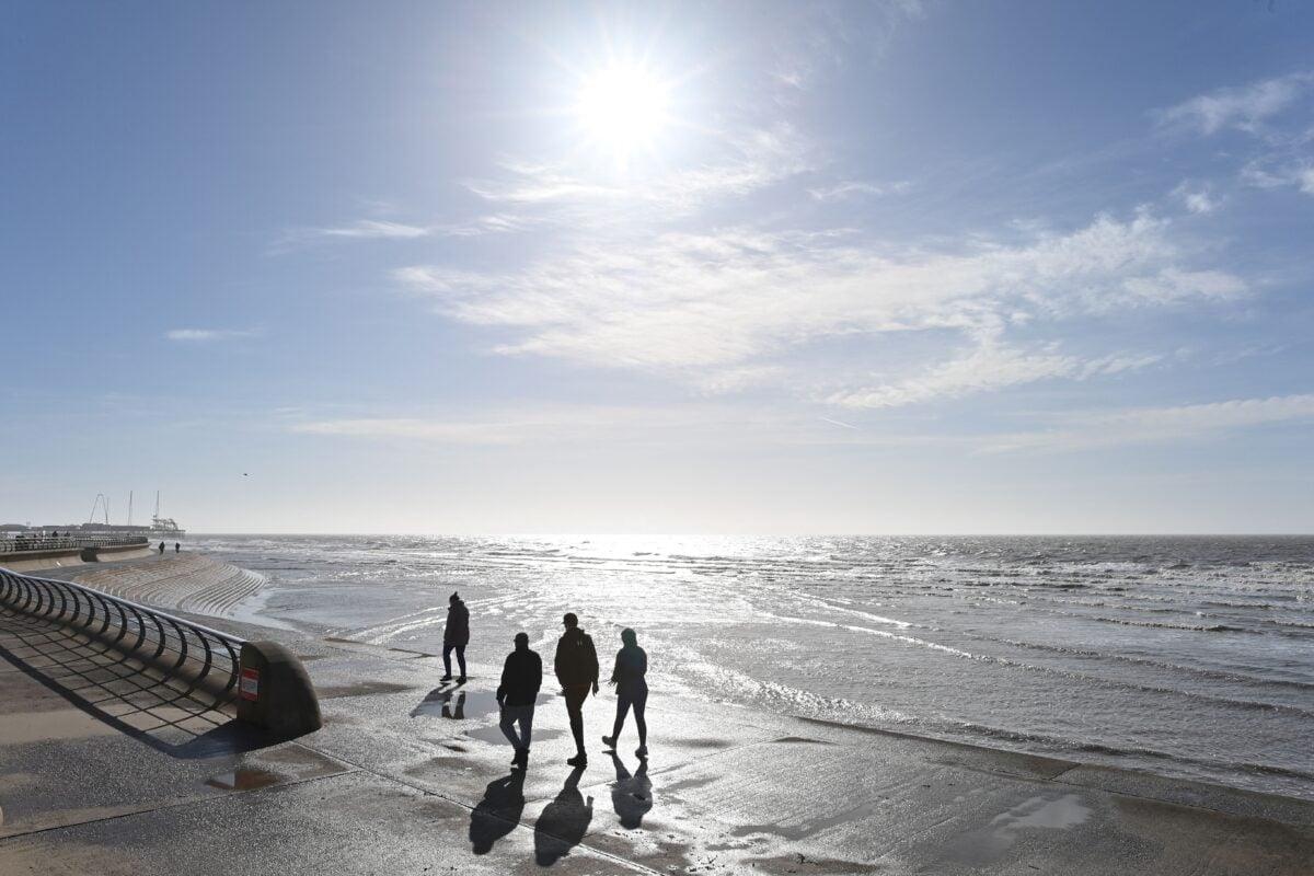 2021年3月16日,在英國蘭開夏郡(Lancashire)黑池(Blackpool),人們沿著海灘散步,享受陽光。(Paul Ellis/AFP via Getty Images)