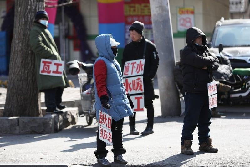 2020年2月25日,在遼寧省瀋陽市,農民工將自己能做的活都寫在牌子上,掛單車和電單車上,等待招聘。(STR/AFP via Getty Images)