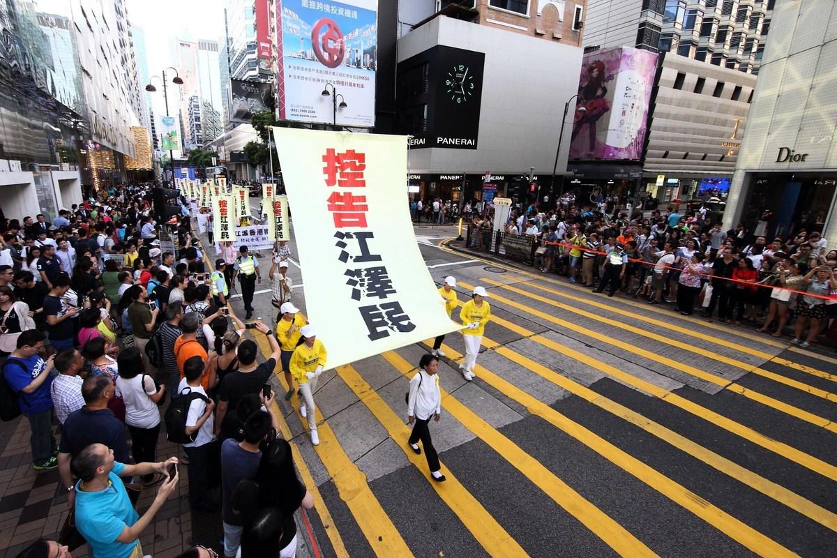 香港2015年7·1大遊行,法輪功隊伍無懼酷熱,打出訴江標語參加遊行。(大紀元)