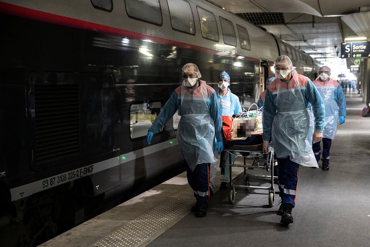 法國疫情仍在惡化。圖為2020年4月1日,巴黎醫護人員護送一位感染中共肺炎的病人到高速火車上,以轉移到其它地區治療。(THOMAS SAMSON/POOL/AFP via Getty Images)