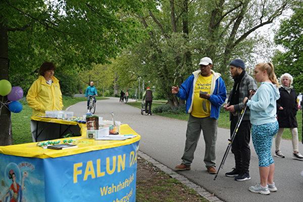 2021年5月13日,弗蘭肯地區的部份法輪功學員在紐倫堡市沃德湖畔舉行集會,路人在展位前仔細聆聽法輪功學員的講解,之後在結束中共的徵簽表上簽名。(大紀元)