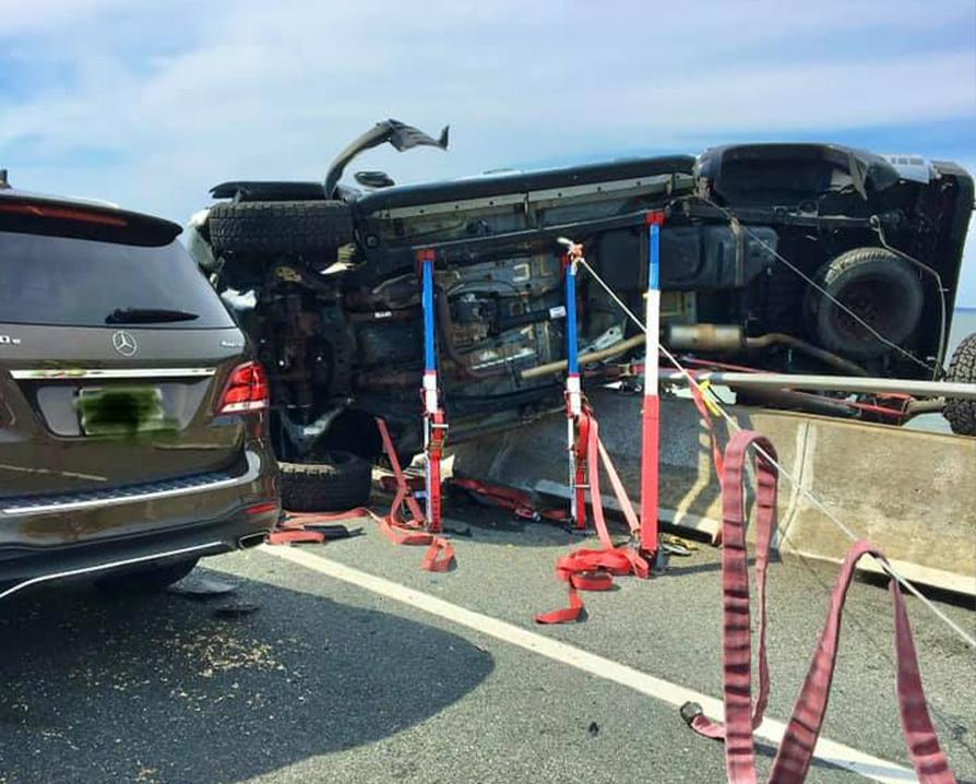 消防人員用工具把衝上橋邊護欄的貨車固定住,以防其墜入海中。(大洋城消防局提供)