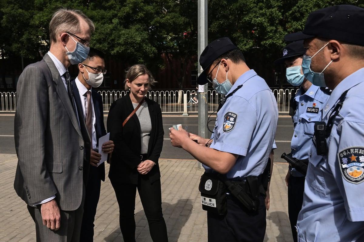 圖為中共警察在法庭外檢查澳洲駐華大使傅關漢(Graham Fletcher)的證件。(NICOLAS ASFOURI/AFP via Getty Images)