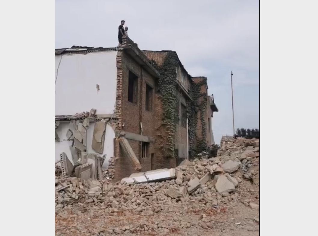 河南省洛陽市洛龍區劉富村被強拆,村民站在房頂對抗拆遷人員。(受訪人提供)