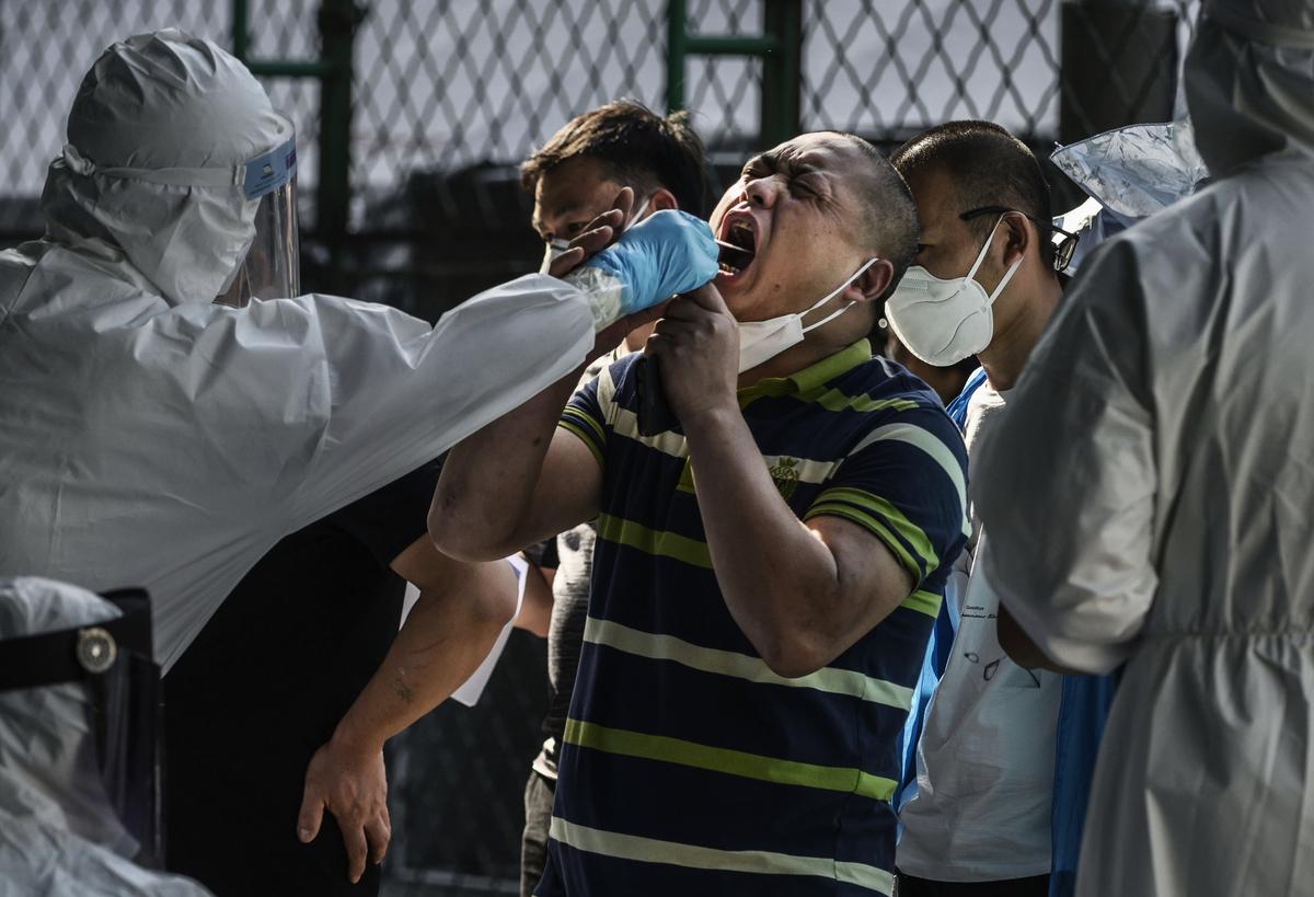 2020年6月16日,中國北京,一名穿全套防護裝備的防疫人員正對民眾進行中共病毒的核酸檢測。(Kevin Frayer/Getty Images)
