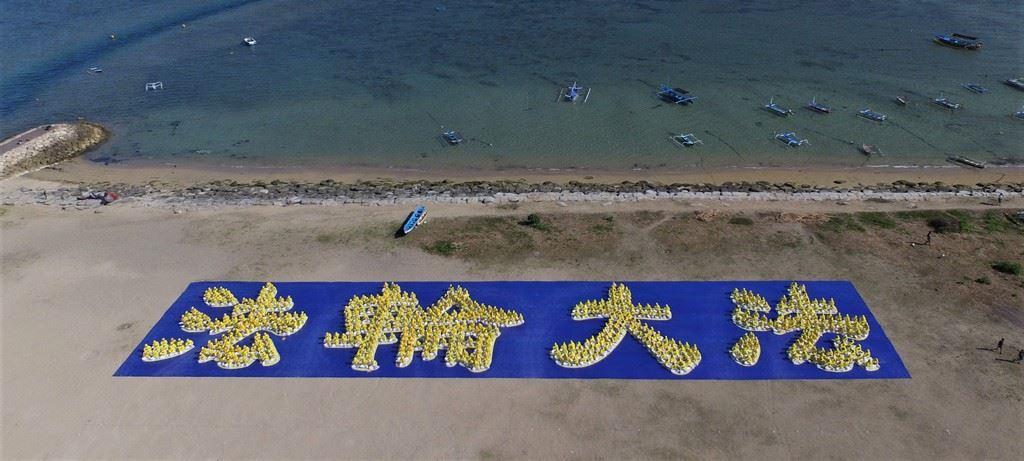 在登巴剎沙努爾海灘上,數百位印尼法輪功學員排成「法輪大法」字型,從上空往下俯覽,場面壯觀。(明慧網)