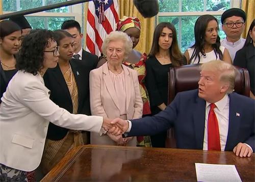 二零一九年七月十七日下午,美國總統特朗普在白宮橢圓形辦公室與來自中國的法輪功學員張玉華女士握手。(白宮新聞影片截圖)