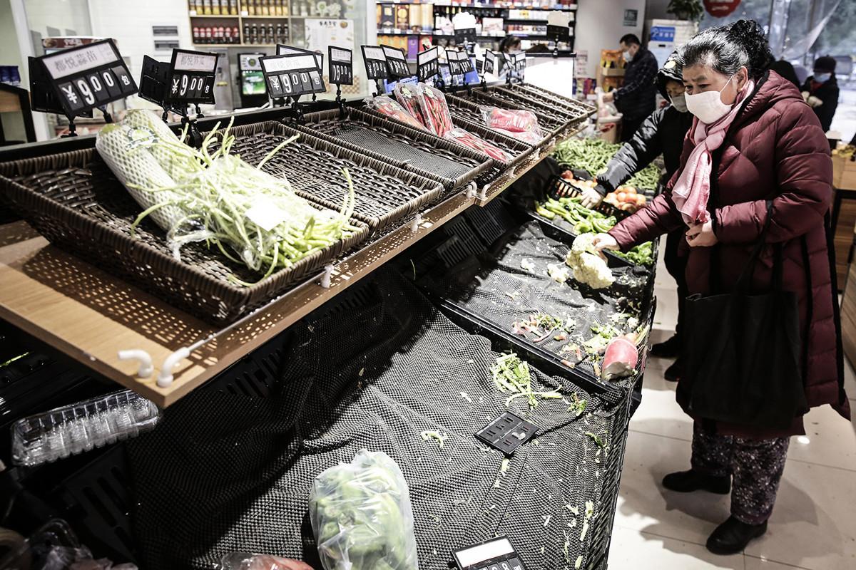武漢市民戴口罩到超市買菜,貨架上的菜被一掃而光。(Photo by Getty Images)