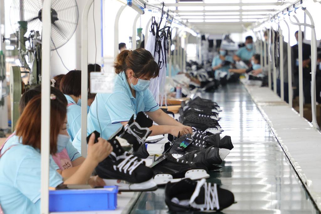 圖為2021年7月15日,中國工人在中國張家口的冰雪運動裝備產業園組裝滑雪靴。(Photo by Lintao Zhang/Getty Images)