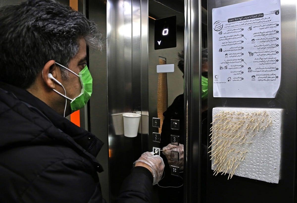 2020年3月4日,一名戴著口罩的伊朗人在德黑蘭用牙籤開電梯,以防感染中共病毒。(ATTA KENARE/AFP)