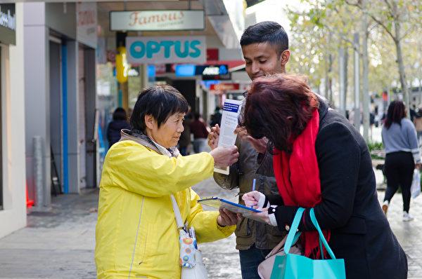 西澳大法弟子露茜在首府珀斯的商業區給過往民眾講真相。(周鑫/大紀元)