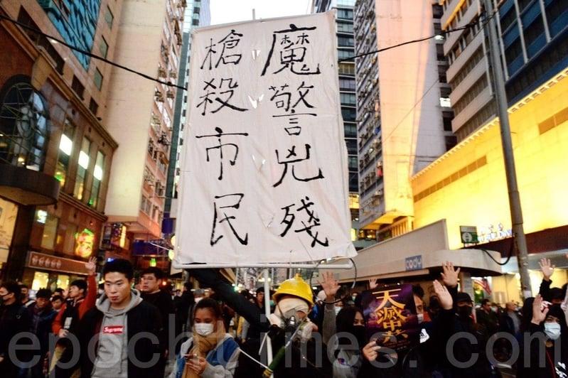 12月8日,香港民陣發起「國際人權日」集會大遊行。遊行隊伍在金鐘軒尼詩道,遊行民眾拿著「魔警凶殘,槍殺市民」的標語。(余天祐/大紀元)