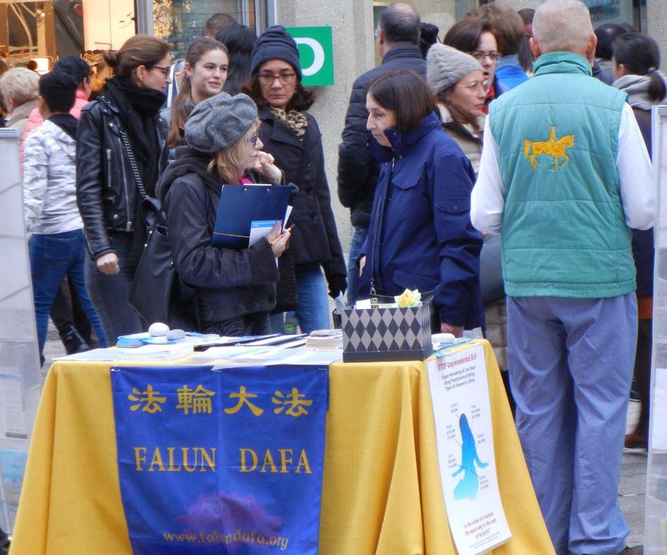 在寒冷的冬天,法輪功學員在日內瓦市中心的商業步行街給人們講真相。(明慧網)