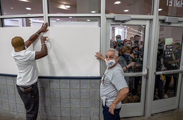 2020年11月4日,密歇根州底特律市中心,投票站工作人員堵上窗戶,擋住質疑選票詐欺的選民,使他們無法看到TCF中心的選票計數區域。(SETH HERALD/AFP via Getty Images)