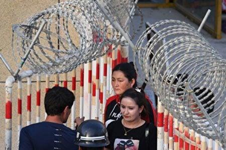 2019年5月31日,一名維吾爾族婦女(中)穿過新疆和田市的一個集市入口。(Greg Baker/AFP via Getty Images)