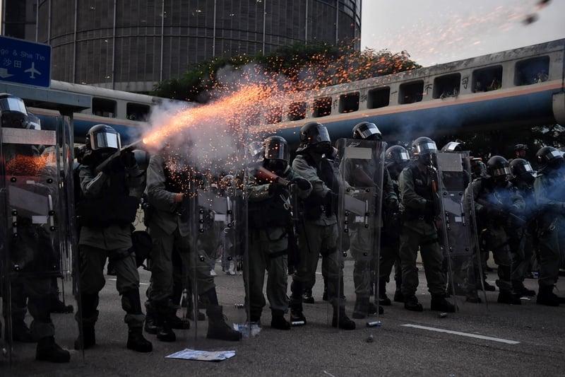 8月24日,港人舉辦「清除雜草 觀塘開花」九龍東觀塘大遊行。防暴警察釋放催淚彈。圖為在香港九龍灣,警方發射催淚彈驅趕民眾。(LILLIAN SUWANRUMPHA/AFP/Getty Images)