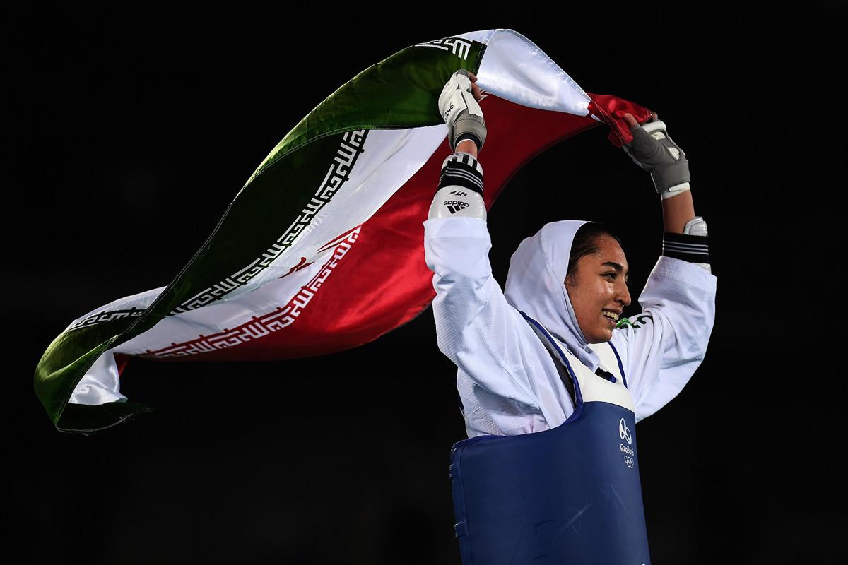 伊朗唯一一名曾贏得奧運獎牌的女運動員阿里薩德(Kimia Alizadeh)宣佈永久離開伊朗。圖為2016年8月18日,阿里薩德在贏得里約奧運跆拳道比賽銅牌之後揮舞伊朗國旗。(Laurence Griffiths/Getty Images)