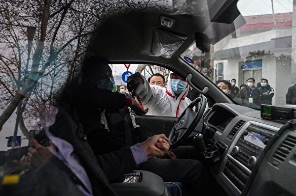 2月1日,世界衛生組織(WHO)專家小組到湖北省疾病預防控制中心時,在入口處一位身穿防護裝備的警衛人員給車內的人測試體溫。(HECTOR RETAMAL/AFP via Getty Images)