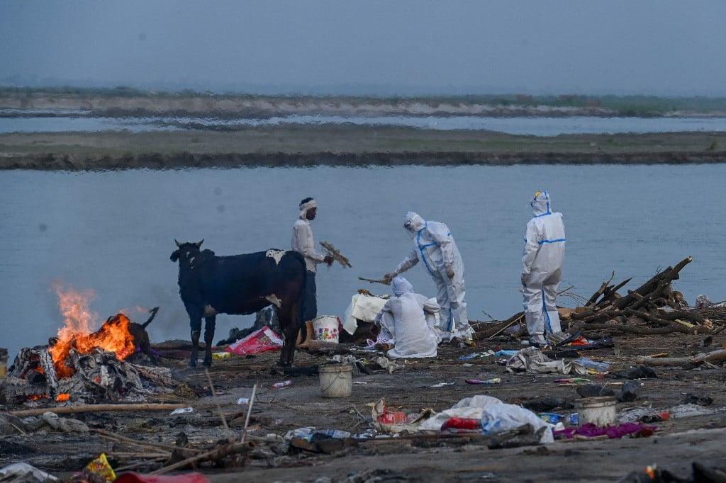 2021年5月5日,印度人身穿防護服在恆河岸邊焚燒染疫病亡的家人屍體。(Prakash SINGH/AFP)