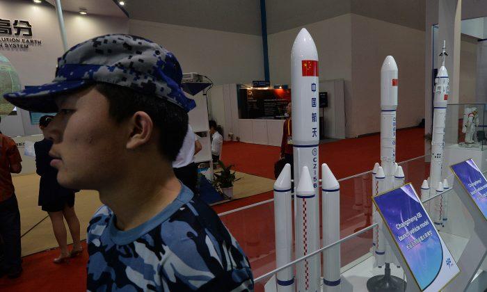 2013年9月24日,一名保安站在中國北京展出的中國火箭模型旁。中共政權正在測試可能很快危及所有軌道衛星的武器。(Mark Ralston/AFP/Getty Images)