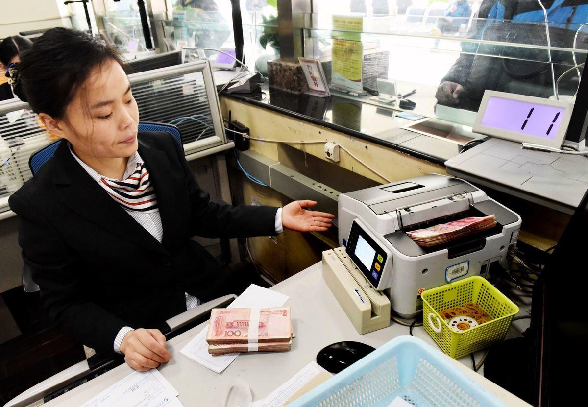 法國科法斯集團發表報告稱,中共打擊影子銀行以減少債務的舉措,致使中小企業融資困難。圖為2016年1月7日,江蘇省連雲港市一家銀行的行員在數鈔票。(STR/AFP/Getty Images)
