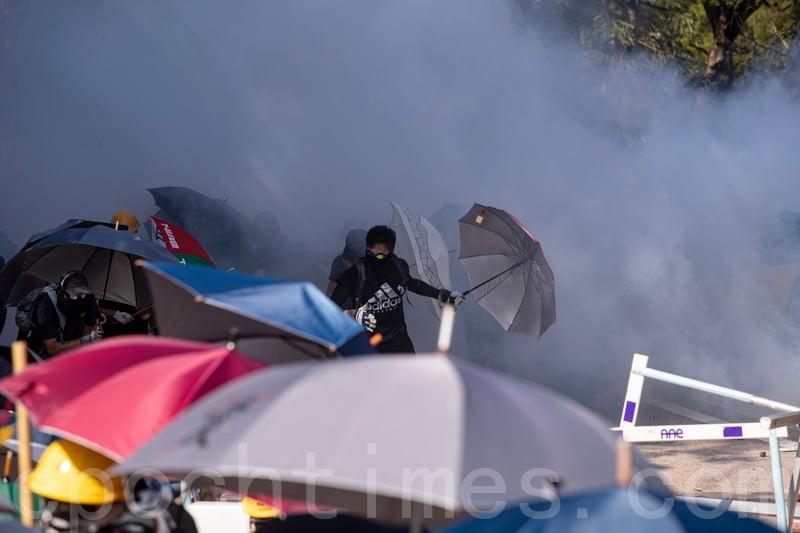 2019年11月11日,香港民間發起全港三罷的「黎明行動」。香港中文大學學生高呼「中大是我家」,拒絕警察進入,警察向學生發射催淚彈。(余鋼/大紀元)