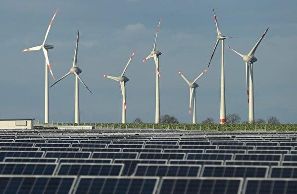 2013年10月30日,德國雲達(Werder)附近的一個太陽能發電廠後面,豎立著風力渦輪機。(Sean Gallup/Getty Images)