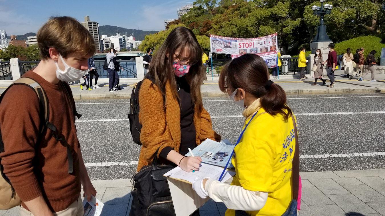2020年11月1日,在日本廣島和平公園裏,民眾在舉報迫害法輪功的元兇江澤民的舉報表上簽名。(明慧網)
