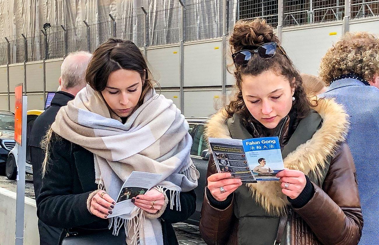 2020年2月29日,在斯德哥爾摩的錢幣廣場上,兩位來自法國的遊客在仔細閱讀法輪功真相傳單。(明慧網)