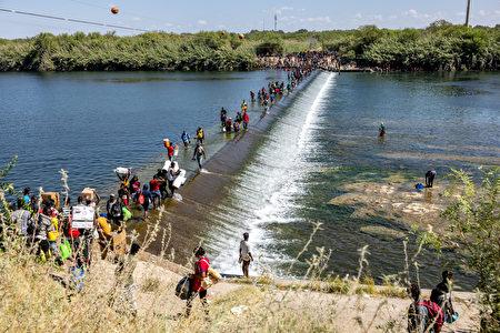 2021年9月17日,移民們走過格蘭德河,攜帶食物和其它用品回到大橋下的臨時營地。(Jordan Vonderhaar/Getty Images)