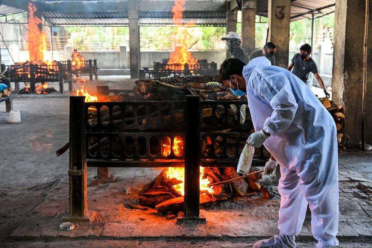 2021年4月23日,印度維拉爾的維賈伊·瓦拉布(Vijay Vallabh)醫院,在一場火災中,13名COVID-19患者被燒死。圖為一個臨時火葬場的工作人員在火化一名COVID-19死者。(PUNIT PARANJPE/AFP via Getty Images)