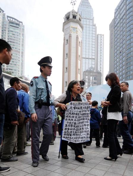 中共三年「掃黑鬥爭」即將開始第二輪、第三輪督導,重點是「打財斷血」。圖為2010年10月23日,中國重慶市,公安人正在驅趕一位手持請願條幅的老婦人,據這位老婦人稱,她的兩個兒子遭「黑打」。(STR/AFP/Getty Images)