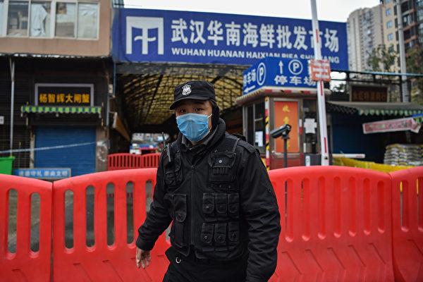 2020年1月25日,一名公安站在中共肺炎的最早起源地──華南海鮮批發市場外。(Hector RETAMAL/AFP)